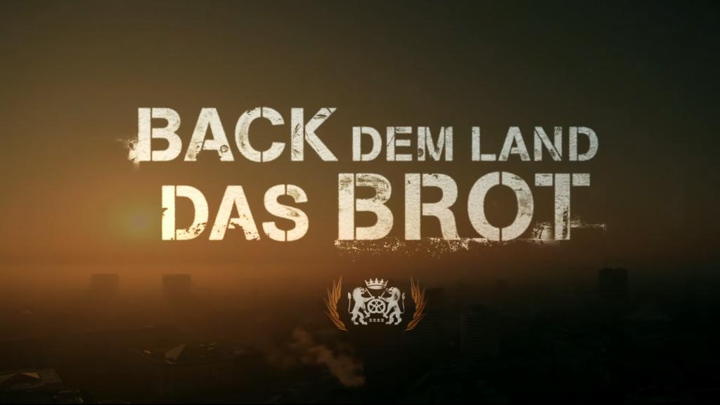 Motivbild: Back dem Land das Brot. Schriftzug mit dem Bäckerwappen im Morgenhimmel mit aufgehender Sonne über einer Stadt.