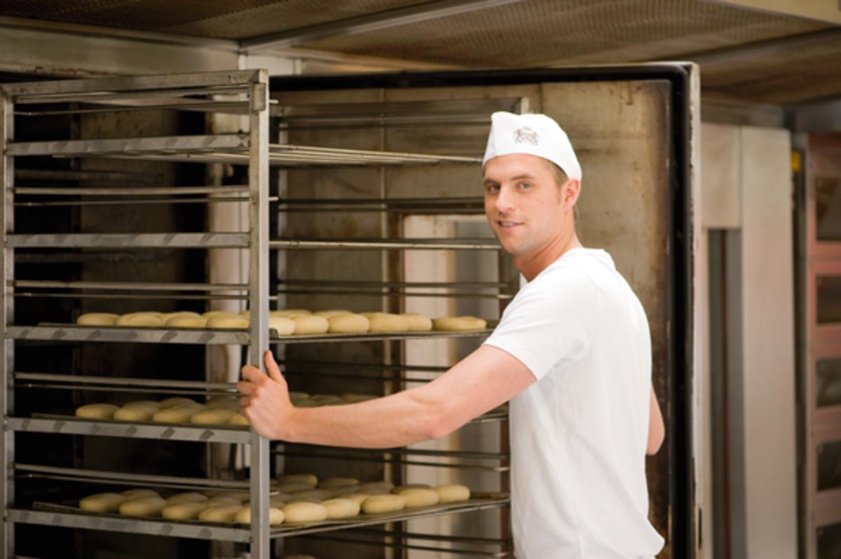 Bäckergeselle beschickt einen Stikkenofen mit einem Stikken Brötchenteiglinge auf Backblechen. Aufgrund der Temperaturleitfähigkeit und des Gewichts werden hier gerne Bleche aus Aluminium verwendet.