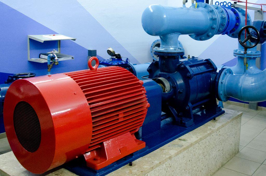 Turbinenhalle eines keinen Wasserkraftwerks. Rot: Generator; Dunkelblau: Turbine; Blau: Wasserleitungen